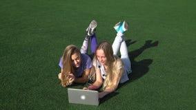 Duas meninas estão encontrando-se no gramado com grama usando o portátil vídeos de arquivo