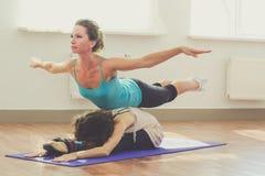 Duas meninas estão fazendo a ioga dentro Foto de Stock Royalty Free