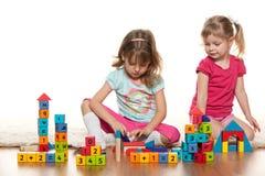 Duas meninas estão jogando no assoalho Fotografia de Stock Royalty Free