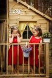 Duas meninas estão levantando em uma casa na árvore Fotos de Stock Royalty Free