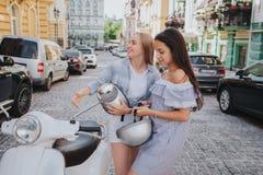 Duas meninas estão montando em uma motocicleta A menina chinesa está em uma parte dianteira A menina moreno está sentando-se no m fotos de stock royalty free