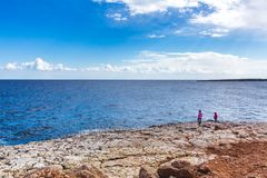 Duas meninas estão na costa de mar bonita em Chipre Uma vista de uma costa de mar em Kavo Greko Aiya nenar Napa, Chipre imagens de stock royalty free