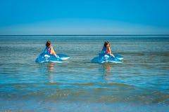 Duas meninas estão nadando em golfinhos bombeados no mar Fotos de Stock