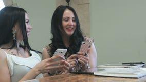 Duas meninas estão olhando fotos em um telefone celular video estoque