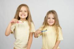 Duas meninas estão preparando-se para escovar os dentes fotografia de stock