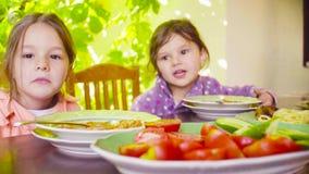 Duas meninas estão sentando-se na tabela no jardim vídeos de arquivo
