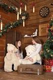 Duas meninas estão sentando-se no assoalho no fundo de uma parede de madeira perto da árvore de Natal Imagens de Stock Royalty Free