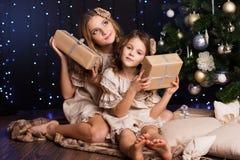 Duas meninas estão sentando-se perto da árvore de Natal imagens de stock royalty free