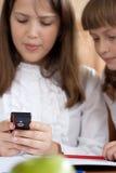 Duas meninas estão usando o close up do telefone móvel Foto de Stock
