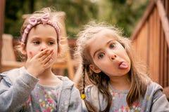 Duas meninas fazem as caras engraçadas Imagens de Stock