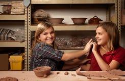 Duas meninas felizes no estúdio da argila imagem de stock royalty free