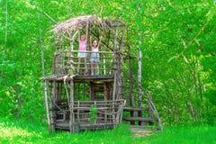 Duas meninas felizes pequenas em uma casa na árvore de madeira em um dia ensolarado As irmãs exultam no verão fotos de stock royalty free