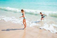Duas meninas felizes pequenas têm muito divertimento na praia tropical que joga junto na água pouco profunda Espirro das crianças Foto de Stock Royalty Free