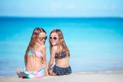 Duas meninas felizes pequenas têm muito divertimento na praia tropical que joga junto Imagem de Stock