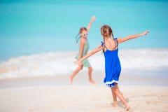 Duas meninas felizes pequenas têm muito divertimento na praia tropical que joga junto Imagens de Stock