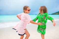 Duas meninas felizes pequenas têm muito divertimento na praia tropical que joga junto Fotografia de Stock Royalty Free
