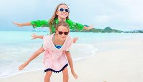 Duas meninas felizes pequenas têm muito divertimento na praia tropical que joga junto Foto de Stock
