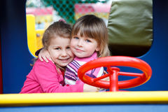 Duas meninas felizes que abraçam no playgroung Fotos de Stock