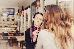Duas meninas felizes que comem bolos e que falam no café Fotos de Stock Royalty Free