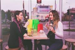Duas meninas felizes que comem bolos e que falam no café Foto de Stock