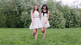 Duas meninas felizes que jogam na grama verde em um fundo de uma árvore de florescência vídeos de arquivo