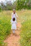 Duas meninas felizes que jogam o corredor no prado verde exterior fotos de stock royalty free