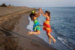 Duas meninas felizes que saltam no ar na praia Fotografia de Stock Royalty Free