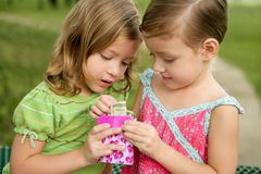 Duas meninas gêmeas pequenas encontram uma nota do dólar Fotos de Stock Royalty Free