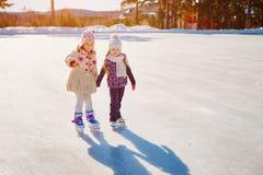 Duas meninas guardam as mãos e o patim Espaço para o texto foto de stock