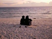 Duas meninas islâmicas no burkini para olhar o por do sol em Maldivas fotografia de stock royalty free