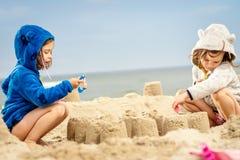 Duas meninas jogam com bonecas em um castelo da areia na praia Imagens de Stock Royalty Free