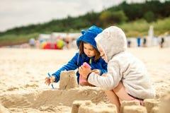 Duas meninas jogam com bonecas em um castelo da areia na praia Fotos de Stock Royalty Free