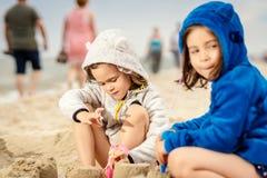 Duas meninas jogam com bonecas em um castelo da areia na praia fotos de stock