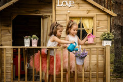 Duas meninas jogam com lata molhando em uma casa na árvore Imagens de Stock