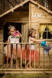 Duas meninas jogam com lata molhando em uma casa na árvore Fotografia de Stock Royalty Free
