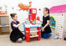 Duas meninas jogam o jogo do papel com a cozinha do brinquedo no centro de dia Fotografia de Stock Royalty Free