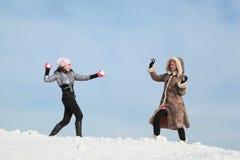 Duas meninas jogam snowballs e riem Fotografia de Stock Royalty Free