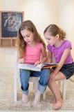 Duas meninas leram um livro Fotos de Stock Royalty Free
