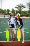 Duas meninas louras consideravelmente de sorriso que vestem camisas quadriculados, tampões e short da sarja de Nimes estão estand imagens de stock