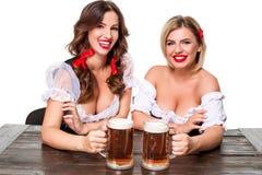 Duas meninas louras e morenos bonitas do caneco de cerveja o mais oktoberfest da cerveja Fotos de Stock