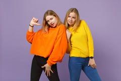 Duas meninas louras novas bonitas das irmãs dos gêmeos na roupa colorida vívida que apontam o polegar ela mesma no isolado na cor imagem de stock