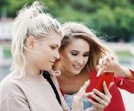 Duas meninas louras novas escolhem algo no telefone fotografia de stock royalty free