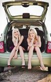 Duas meninas louras que sentam-se no tronco de carro quebrado Foto de Stock Royalty Free