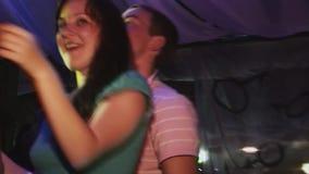 Duas meninas morenos novas dançam com o menino no clube noturno spotlights Sorriso cheering Partido da noite vídeos de arquivo