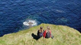 Duas meninas na caminhada da Irlanda nos penhascos de Kilkee em um dia ensolarado - opinião aérea do zangão video estoque