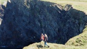 Duas meninas na caminhada da Irlanda nos penhascos de Kilkee em um dia ensolarado - opinião aérea do zangão filme