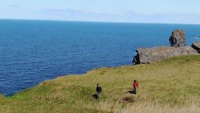 Duas meninas na caminhada da Irlanda nos penhascos de Kilkee em um dia ensolarado - opinião aérea do zangão vídeos de arquivo