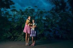Duas meninas na floresta no nighttime Fotos de Stock Royalty Free