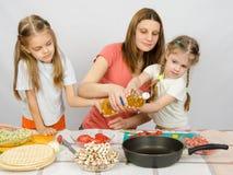 Duas meninas na mesa de cozinha com o entusiasmo para ajudar minha mãe a derramar o óleo vegetal em uma frigideira fotos de stock royalty free