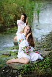 Duas meninas na roupa nacional ucraniana com as grinaldas do fluxo Fotos de Stock